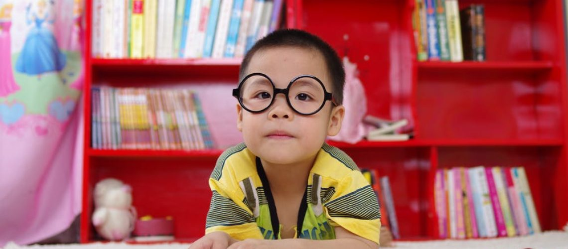 little boy sitting in front of bookshelf looking up from reading a book